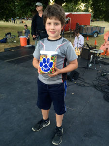 Owen Randall won this jar of candy by guessing it contained 1,506 Skittles. The contest was sponsored by Trinity Lutheran School, as part of Concordia Neighborhood Association's booth at National Night out, and Owen was within 17 Skittles of the correct answer. His parents report he is sharing the prize.